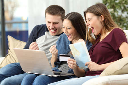 Foto de Three excited friends buying a trip on line with a credit card and a laptop sitting on a couch in the living room at home - Imagen libre de derechos