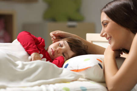 Photo pour Proud mother watching to sleep on the bed to her daughter in a bedroom at home - image libre de droit