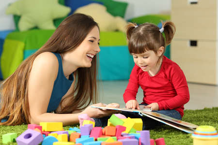 Foto de Mother and toddler playing together with a book lying on the floor in the bedroom at home with a colorful background - Imagen libre de derechos