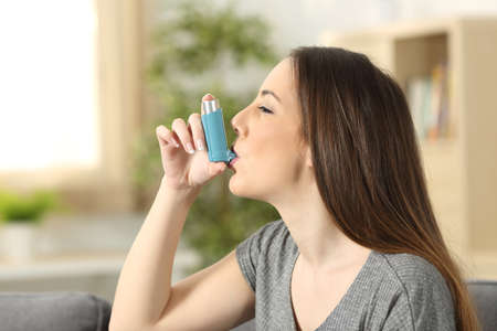 Photo for Side view of an asthmatic woman using an inhaler sitting on a couch in the living room at home - Royalty Free Image