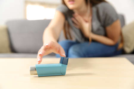 Foto de Girl suffering asthma attack reaching inhaler sitting on a couch in the living room at home - Imagen libre de derechos