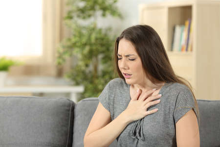 Foto de Woman suffering respiration problems sitting on a couch in the living room at home - Imagen libre de derechos