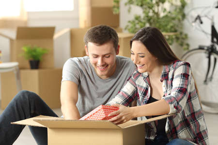 Photo for Happy casual couple sitting on the floor unpacking a box while moving house  in the living room - Royalty Free Image