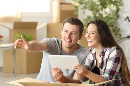 Photo for Happy couple moving house together planning on line with a tablet sitting on the floor at home with boxes in the background - Royalty Free Image