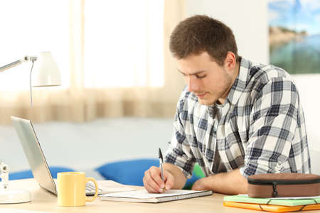 Photo pour Portrait of a student writing in a notebook doing homework in a desk in his room - image libre de droit