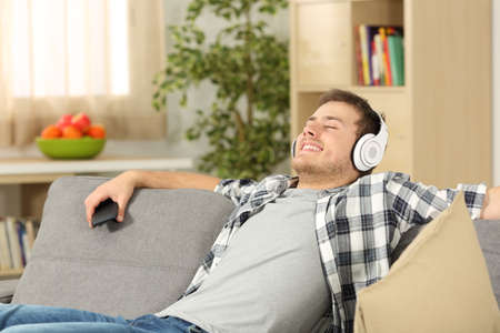 Foto de Single casual man with eyes closed listening to music on line from a smart phone sitting on a sofa in the living room in a house interior - Imagen libre de derechos