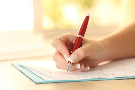 Photo pour Close up of a woman hand using a pen to filling form on a table - image libre de droit