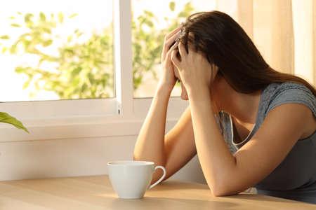 Photo pour Single sad woman covering face sitting in a table at home - image libre de droit