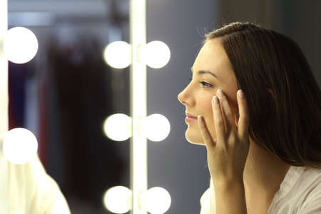 Photo pour Side view portrait of a single woman checking for wrinkles looking at a make up mirror - image libre de droit