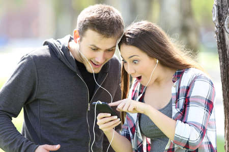 Photo pour Amazed couple standing listening to music on line and watching media content in a smart phone outdoors in a park - image libre de droit