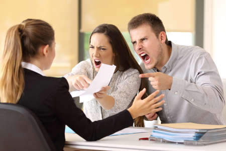 Foto de Angry couple claiming and shouting to an office worker - Imagen libre de derechos
