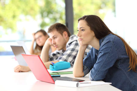 Photo for Side view of three tired students listening a boring lesson sitting in a desk at classroom - Royalty Free Image