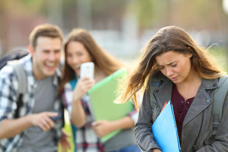Foto de Bullying victim being video recorded on a smartphone by classmates in the street with a unfocused background - Imagen libre de derechos