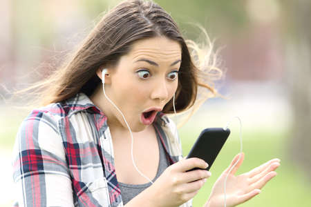 Foto de Amazed girl listening on line music and watching media content outdoors in a park - Imagen libre de derechos