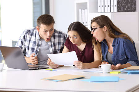 Photo pour Three amazed employees reading a paper document at office - image libre de droit