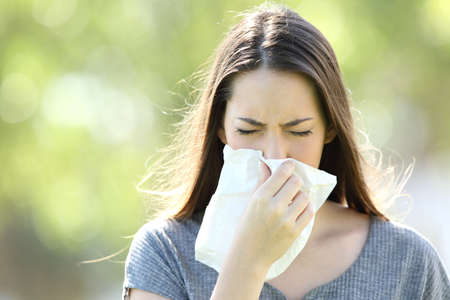 Foto de Front view of a single girl sneezing and blowing in a wipe outdoors with a green background - Imagen libre de derechos