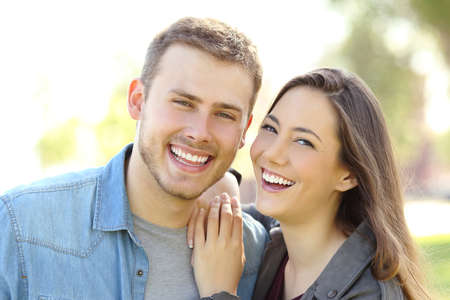 Photo for Front view of a couple posing outdoors with perfect smile and white teeth and looking at you in a park with a green background - Royalty Free Image