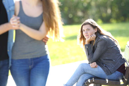 Photo pour Single envious girl sitting on a bench and seeing an affectionate couple who is walking in a park - image libre de droit