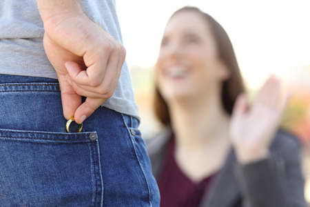 Foto de Cheater hiding wedding ring in a pocket in foreground while is dating with his lover outdoors - Imagen libre de derechos