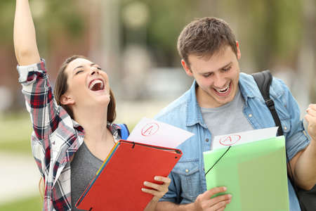 Foto de Two excited students with approved exams in the street - Imagen libre de derechos