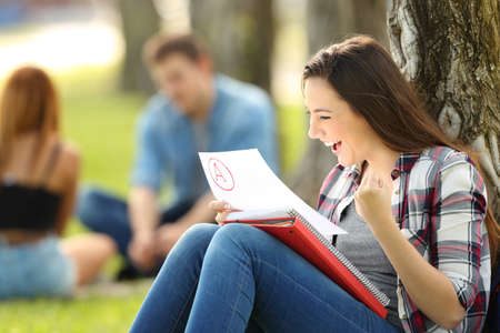 Foto de Excited student checking an approved exam sitting on the grass in a park with unfocused people in the background - Imagen libre de derechos