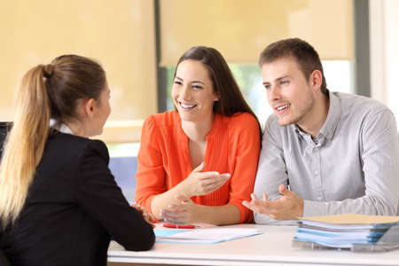 Photo for Two happy customers having a conversation with an office worker - Royalty Free Image
