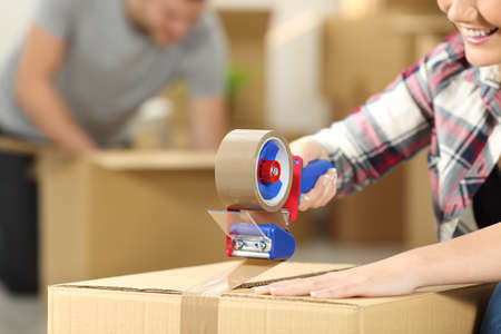 Photo for Close up of a happy couple moving home packing boxes and sealing with tape sitting on the floor - Royalty Free Image