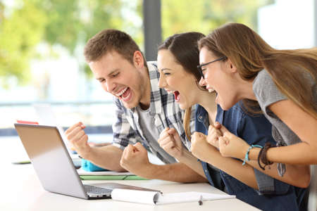 Photo pour Side view of three excited students reading good news together on line in a laptop sitting in a desk in a classroom - image libre de droit