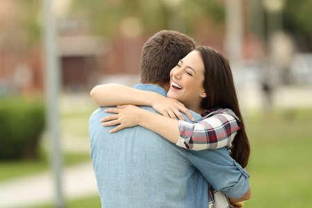 Photo pour Happy encounter of two friends hugging outdoors in a park - image libre de droit
