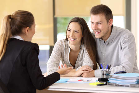Photo pour Happy couple talking with a real estate agent at office - image libre de droit