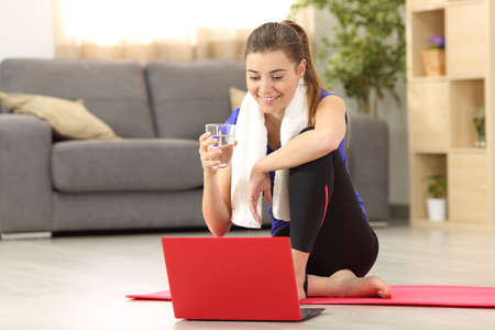 Foto de Front view of a fitness woman holding a water glass watching on line tutorials sitting on the floor in the living room at home - Imagen libre de derechos