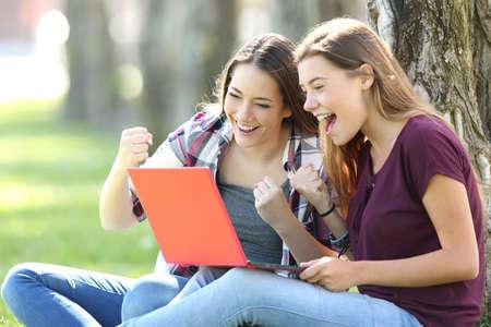 Foto de Excited teens receiving good news on line sitting on the grass in a park - Imagen libre de derechos