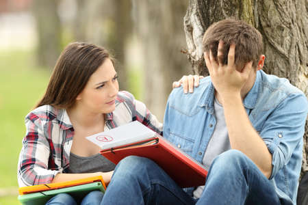 Photo for Friend comforting to a sad student with failed exam sitting on the grass in a park - Royalty Free Image