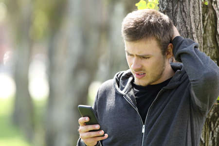 Foto de Confused single teen reading a message in a smart phone outdoors in a park - Imagen libre de derechos