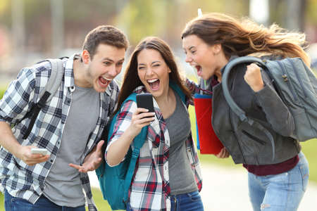 Photo pour Front view of three excited students receiving good news on line in a mobile phone in an university campus or street - image libre de droit