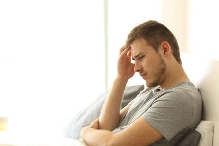 Foto de Sad single man lamenting sitting on the bed on the bed of an hotel room or home - Imagen libre de derechos