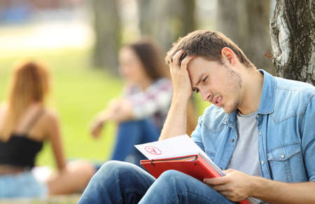 Photo pour Single sad student checking a failed exam sitting on the grass in a park with unfocused people in the background - image libre de droit