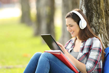 Photo pour Single student studying listening on line lessons sitting on the grass in a park with a green background - image libre de droit