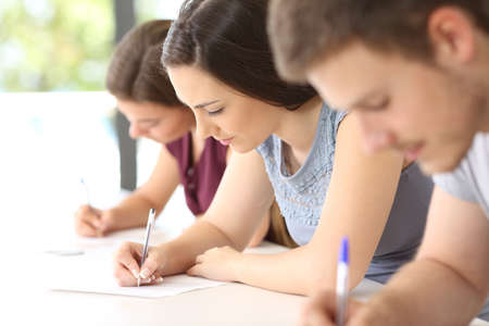 Photo for Close up of three concentrated students doing an exam in a classroom - Royalty Free Image