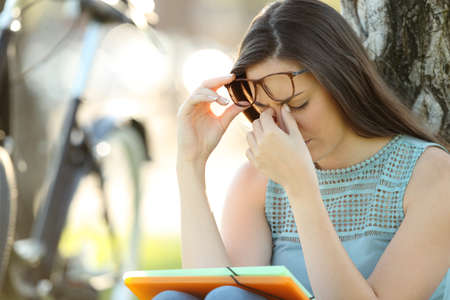 Photo for Single student wearing eyeglasses suffering eyestrain while is studying in a park - Royalty Free Image