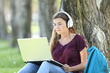 Foto de Single teen girl studying watching video tutorials on line in a laptop sitting on the grass leaning in a tree in a park - Imagen libre de derechos