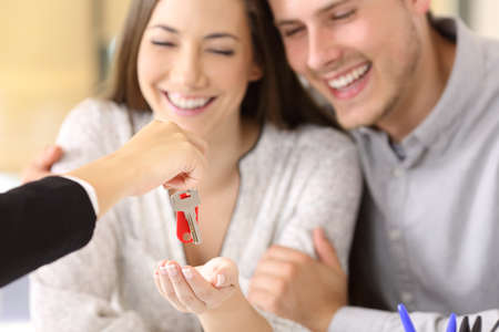 Photo for Close up of a happy homeowners receiving their new house keys from a real estate agent at office - Royalty Free Image