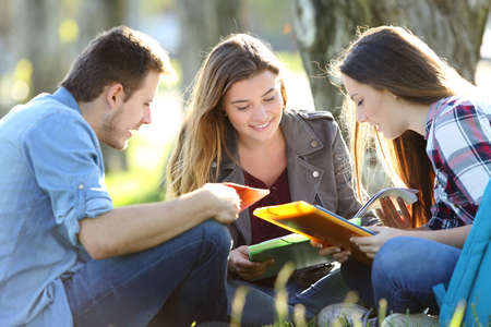 Foto de Three students studying reading notes together outdoors sitting on the grass - Imagen libre de derechos