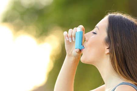 Foto de Side view of a woman using an asthma inhaler outdoors with a green background - Imagen libre de derechos