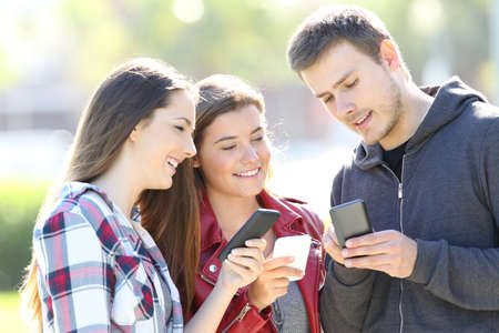 Foto per Three friends talking together and holding everyone their smart phones standing in the street - Immagine Royalty Free