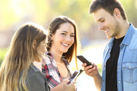 Photo for Three teens using their smart phones and one of them looking at you in the street - Royalty Free Image