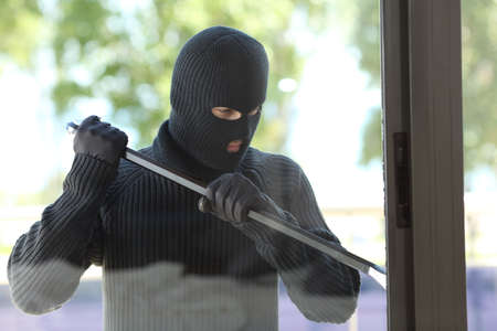 Foto de Thief wearing black mask trying to open a house window with a lever - Imagen libre de derechos