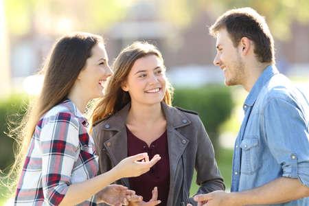 Foto de Three happy friends having a conversation and laughing in the street - Imagen libre de derechos