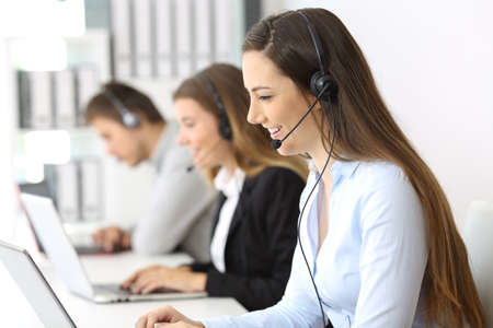 Photo pour Side view of a telemarketer working on line at office with other workers in the background - image libre de droit
