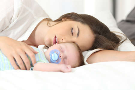 Photo pour Tired mother sleeping with her baby on a bed at home - image libre de droit
